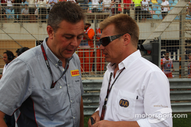 Mario Isola, Pirelli Racing Manager on the grid with Mika Salo, FIA Steward