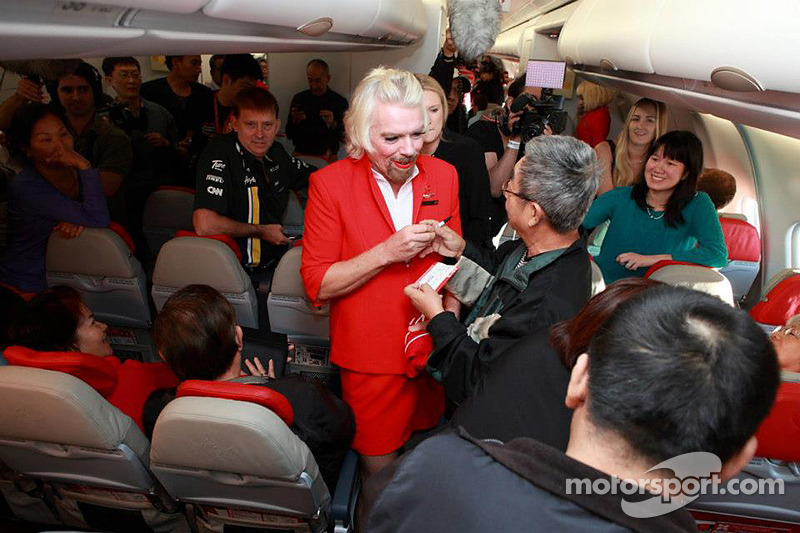 Sir Richard Branson serves as a flight attendant on Air Asia flight after losing a bet with Caterham