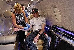 Kurt Busch is checked by a nurse during the flight to Charlotte