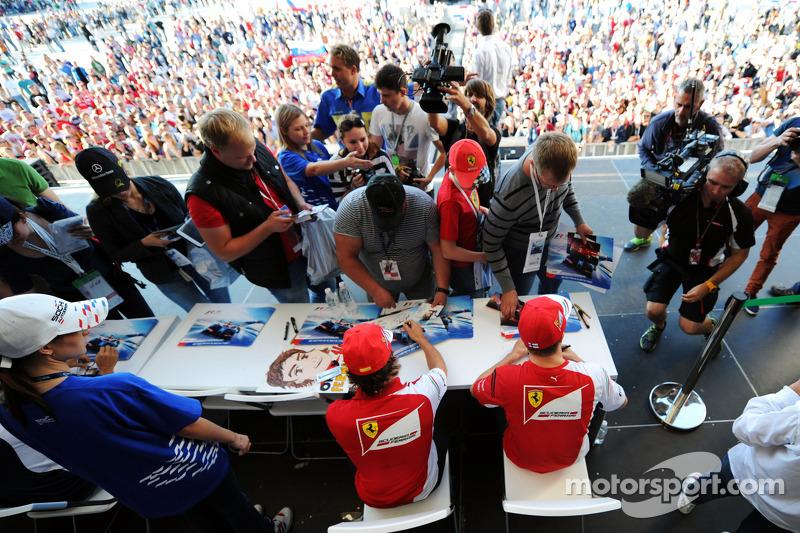 (L to R): Fernando Alonso, Ferrari and team mate Kimi Raikkonen, Ferrari sign autographs for the fans at the Fanzone