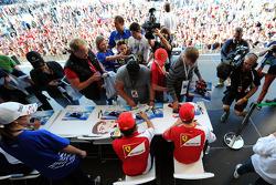 (Da sinistra a destra): Fernando Alonso, Ferrari e il compagno di squadra Kimi Raikkonen, Ferrari firmano autografi nella Fanzone