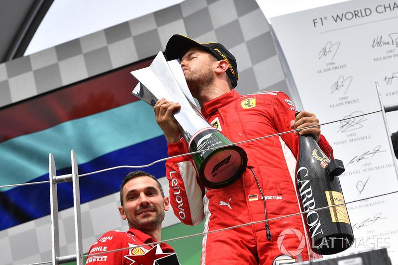 El ganador en Canadá Sebastian Vettel, lo celebra en el podio y besa el trofeo