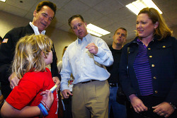 President of NASCAR Brian France talks with California governor Arnold Schwarznegger and his son Christopher