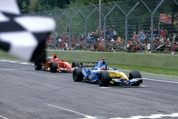 Fernando Alonso takes the checkered flag in front of Michael Schumacher