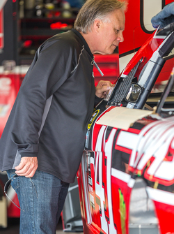 Gene Haas looks at the car of Regan Smith