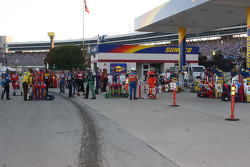 Team members wait at the gas pumps after pit stops