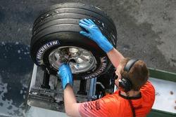 McLaren team member washes tires