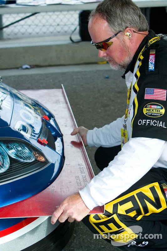 Un employé du NASCAR vérifie l'avant de la voiture avec un modèle