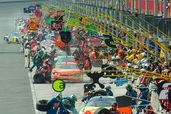 Race teams services the cars along pit lane