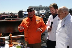 Chef Mario Batali, Eddie Gossage and Bruton Smith stand in front of a grill