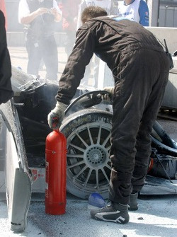 Mechanics put out the fire in the car of Bruno Spengler after a massive engine blow up