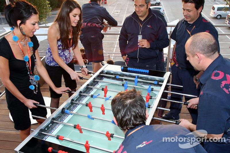 Des membres de la Scuderia Toro Rosso avec des jeunes femmes de la Formule 1