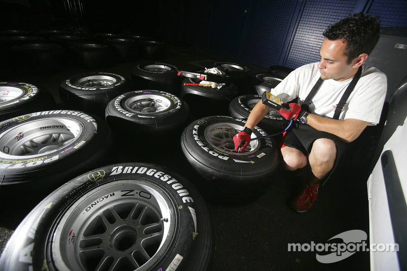 Un membre de l'équipe ART Grand Prix vérifie les pneus