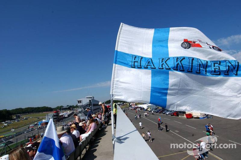 Les fans dévoués de Mika Hakkinen agitent le drapeau d'arrivée dans la tribune