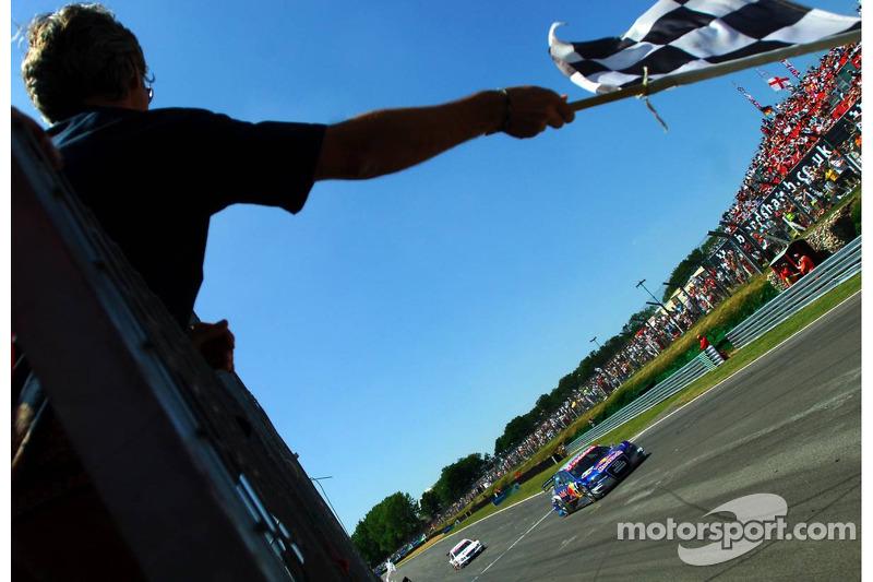 Mattias Ekström passe devant le drapeau à damier agité par Damon Hill
