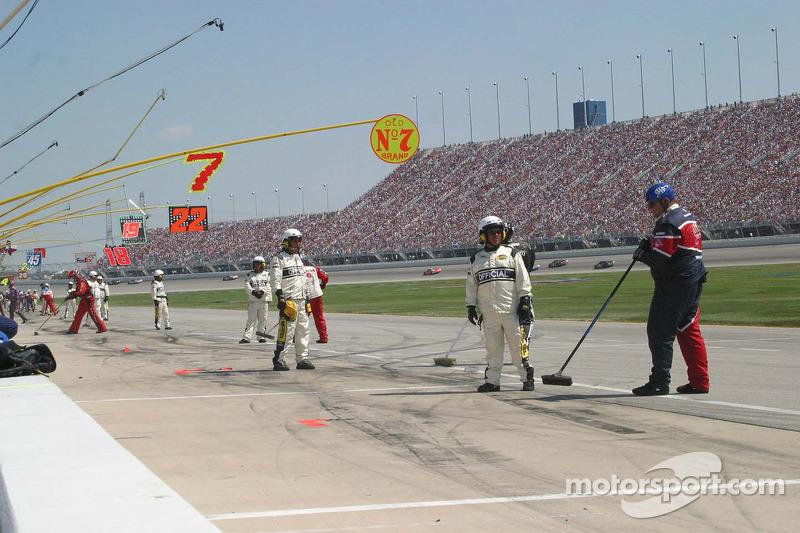 Des employés de NASCAR gardent un œil sur des membres de l'équipe qui nettoient les écrous de roue