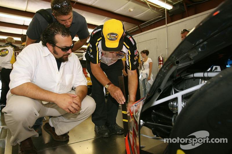 Matt Patricia, Linebacker Coach pour les New England Patroits, et Dave Granito, assistant de l'entraînement de sport pour les New Englet Patroits, regardent un employé de NASCAR qui inspecte une voiture de course