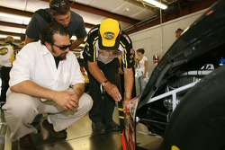 Matt Patricia, Linebacker Coach for the New England Patroits, and Dave Granito, Assistant Athletic Trainer for the New England Patroits, watch a NASCAR offical inspect a race car