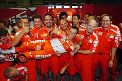 Race winner Loris Capirossi celebrates with Ducati team members