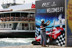 A fisher stands in front of an advertising banner in downtown Istanbul