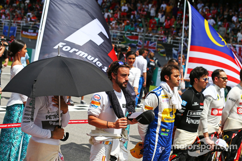 Lewis Hamilton, Mercedes AMG F1 and Fernando Alonso, McLaren as the grid observes the national anthem