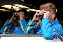 Renault F1 Team mechanics look through binoculars