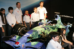 Jenson Button and Rubens Barrichello pose with kids and the Honda F1 Racing RA107 in its new livery