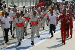 McLaren Mercedes run to greet their drivers at parc ferme