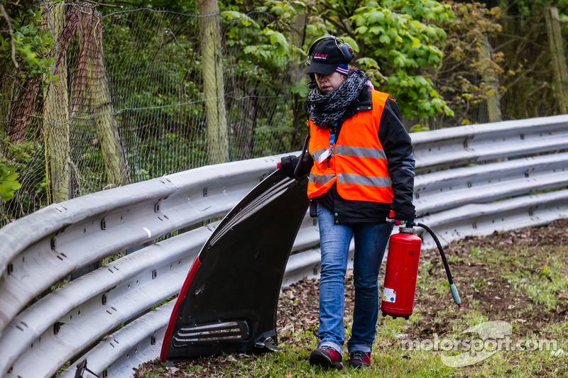 Seorang marshal lapangan membersihkan trek