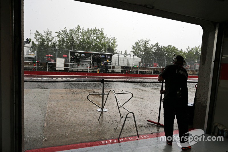 Sahara Force India F1 Team mechanic protects the pit garage from the rain
