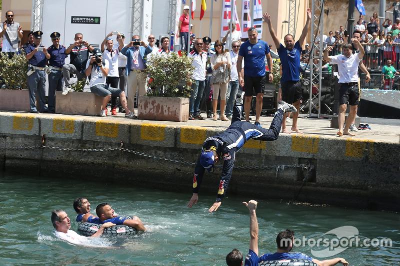 Members of Volkswagen Motorsport jump into the marina