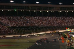 Lapped cars roll into the pits shortly after dark in the Coca Cola 600