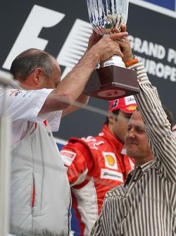 Michael Schumacher da la mano a Ron Dennis y el trofeo de constructores