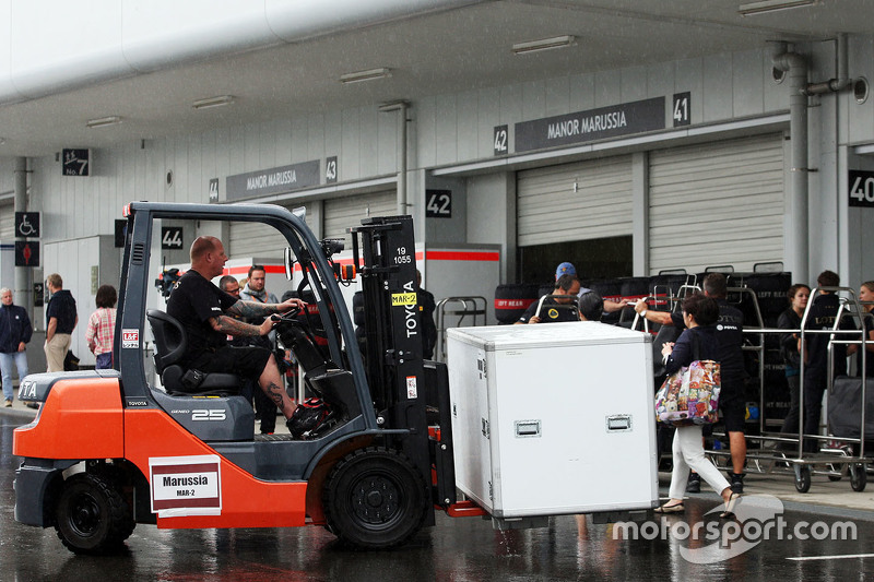 Lotus F1 Team mechanic with forklift truck in the paddock