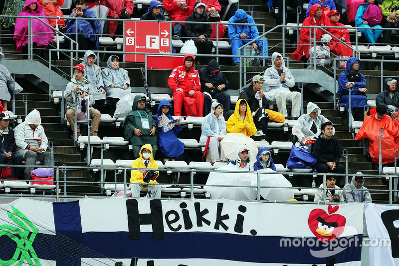 Fans in the grandstand and a banner for Heikki Kovalainen