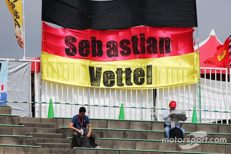 Fans in the grandstand and a banner for Sebastian Vettel, Ferrari