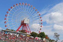 Fans in the grandstand and the big wheel
