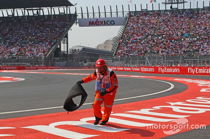 Ein Sportwart räumt Trümmerteile von Sebastian Vettel, Ferrari, weg