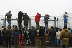 Photographers shoot at the perimeter fence
