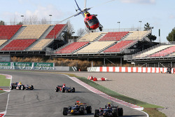 Red Bull Racing and Scuderia Toro Rosso cars are filmed by a low flying helicopter
