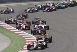 Vitaly Petrov leads the field through turn one on the opening lap of the race