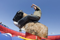A fan enjoys a ride on the mechanical bull at the Jim Beam hospitality tent