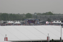 A large crowd watches a concert in the rain in the infield