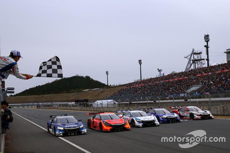 Takuma Sato zwaait de zwart-wit geblokte vlag voor de Super GT Honda-deelnemers