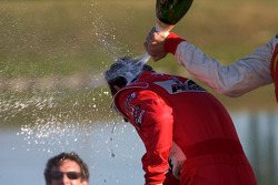 Podium: Justin Wilson sprays champagne on Helio Castroneves