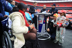 Sebastian Vettel poses for an autograph with a young fan