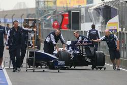Williams team push the car down the pit lane
