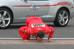 Race winner Helio Castroneves kisses the yard of bricks