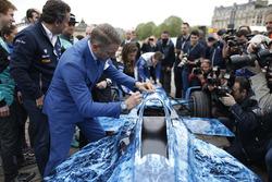 Funzionari e piloti firmano la livrea iceberg su una vettura di Formula E che sarà messa all'asta per raccogliere fondi per combattere il cambiamento climatico