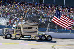 The traditional American flag is pulled around the track